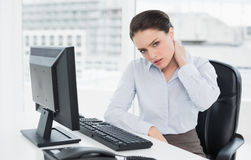 Businesswoman with neck pain sitting at office Stock Photo