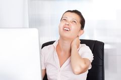 Businesswoman With Neck Pain. Young Businesswoman Suffering From Neck Pain In Front Of Computer stock photo