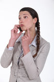 Businesswoman needs to make decision. Businesswoman on the phone trying to make a decision Royalty Free Stock Photography