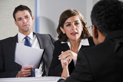 Businesswoman negotiating with men. Diverse business people conversing and negotiating, focus on businesswoman, 40s Royalty Free Stock Photo