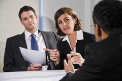 Businesswoman negotiating with men. Diverse business people conversing and negotiating, focus on businesswoman, 40s Royalty Free Stock Images