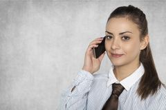 Businesswoman is negotiating on a mobile phone. Isolated on the background Stock Photos