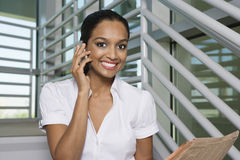 Businesswoman With Newspaper On Call Royalty Free Stock Images