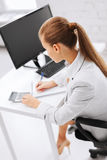 Businesswoman with notebook and calculator Stock Image