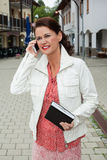Businesswoman with Notebook Talking on Cell Phone Stock Photo