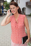 Businesswoman with Notebook Talking on Cell Phone Royalty Free Stock Images