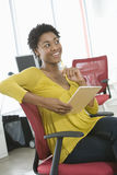 Businesswoman With Notepad And Pencil Sitting On Chair Stock Photo