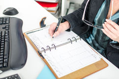 Businesswoman noting an appointment in her diary Stock Photo