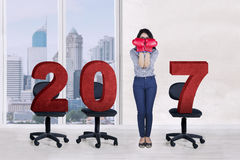 Businesswoman with number 2017 and chairs at office Stock Photography