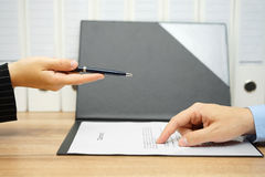 Businesswoman offer a pen over a contract to client Stock Photography