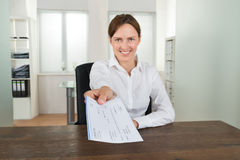 Businesswoman Offering Cheque In Office Stock Images