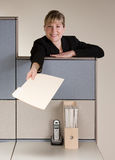 Businesswoman offering file folder. Happy businesswoman offering file folder over cubicle wall Royalty Free Stock Images
