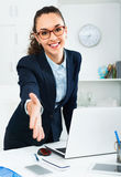 Businesswoman offers hand for greeting in  office Stock Photography