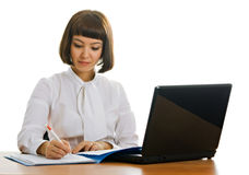 Businesswoman in office. Girl in the office with the computer and working papers Royalty Free Stock Image