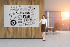 Businesswoman in an office with a business plan poster Royalty Free Stock Images