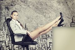 Businesswoman in office chair with her feet up on Royalty Free Stock Photography