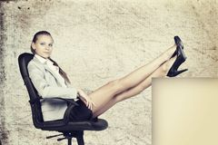 Businesswoman in office chair with her feet up on Stock Image