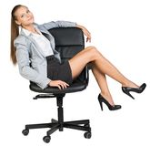 Businesswoman on office chair with her legs over Royalty Free Stock Image