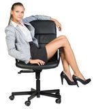 Businesswoman on office chair with her legs over Stock Image