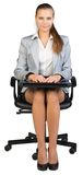 Businesswoman on office chair, holding closed Stock Photos