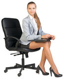 Businesswoman on office chair, holding closed Stock Image