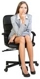Businesswoman on office chair holding finger to Royalty Free Stock Photography
