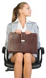 Businesswoman on office chair, holding suitcase Royalty Free Stock Images