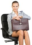 Businesswoman on office chair, holding suitcase Royalty Free Stock Photo