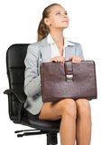 Businesswoman on office chair, holding suitcase Stock Image