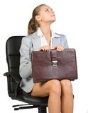 Businesswoman on office chair, holding suitcase Royalty Free Stock Image
