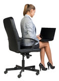 Businesswoman on office chair, with laptop Royalty Free Stock Images