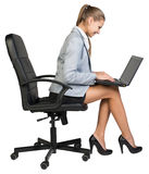 Businesswoman on office chair operating laptop Royalty Free Stock Image