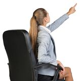 Businesswoman on office chair, pointing finger up Stock Images
