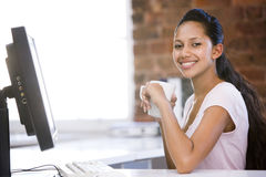 Businesswoman in office drinking coffee Stock Photography