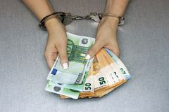 Criminal hands locked in handcuffs. Close-up view. Businesswoman in office in handcuffs holding a bribe of euro banknote. Close-up woman hands in handcuffs stock photo