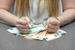 Criminal hands locked in handcuffs. Close-up view. Businesswoman in office in handcuffs holding a bribe of euro banknote. Close-up woman hands in handcuffs stock photography