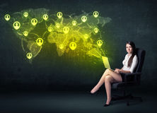 Businesswoman in office with laptop and social network world map Stock Images