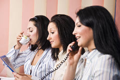 Businesswoman office life. Three businesswomen in office do works,first woman speaking at phone,second reading something and last drinking a cup of coffee,focus stock image