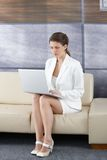 Businesswoman in office lobby with laptop Royalty Free Stock Photo