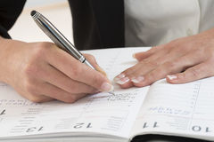 Businesswoman in office noting an appointment in her diary Royalty Free Stock Photography