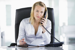 Businesswoman in office with personal organizer. Open on telephone Stock Photos