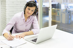 Businesswoman in the office on the phone with headset, Skype Stock Photos