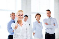 Businesswoman in office showign thumbs up Stock Images