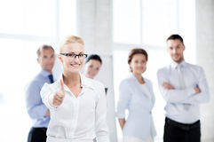 Businesswoman in office showign thumbs up Stock Photos