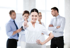 Businesswoman in office showing thumbs up Royalty Free Stock Images