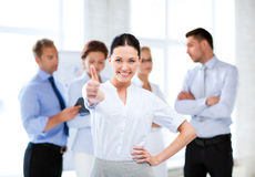 Businesswoman in office showing thumbs up Stock Image