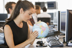 Businesswoman in office space with desk globe Stock Photo