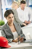 Businesswoman in office using smartphone Stock Image