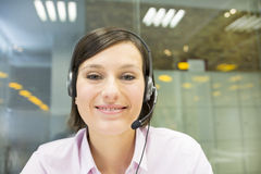 Businesswoman in the office on videoconference with headset, Sky Stock Image