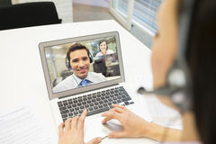Businesswoman in the office on videoconference with headset, Sky Royalty Free Stock Photography